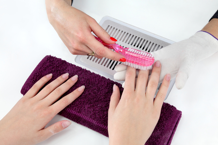 Finger nail treatment, brushing dust from fingers in beauty\ salon
