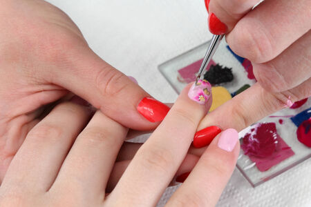 Finger nail treatment, painting flower with brush and lacquer photo