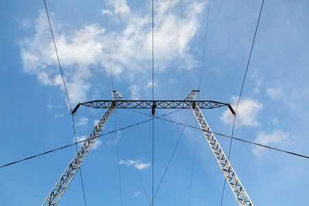 over voltage: High voltage electricity pylon over blue sky and white clouds
