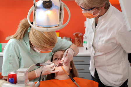 Dentist student drilling  tooth of a young patient with professor looking, real people