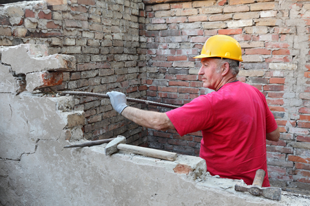 demolishing: Construction worker demolishing old brick wall with crow bar tool