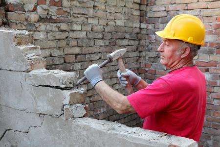 cincel: Trabajador de la construcci�n a demoler pared de ladrillo antiguo con la herramienta de cincel y martillo