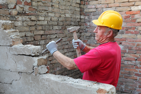 manual job: Construction worker demolishing old brick wall with chisel tool and hammer