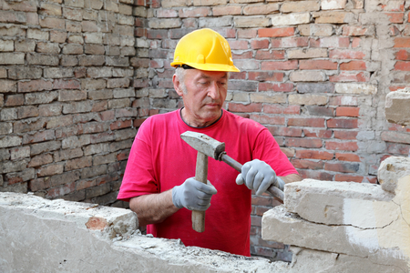 Construction worker demolishing old brick wall with chisel tool and hammer, real people Standard-Bild