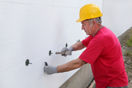 Worker placing expansion anchor to styrofoam sheet insulation of the wall with hammer