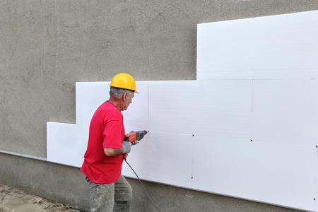 Worker boren piepschuim plaat isolatie aan de muur Stockfoto