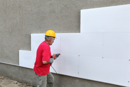 Worker drilling styrofoam sheet insulation on the wall