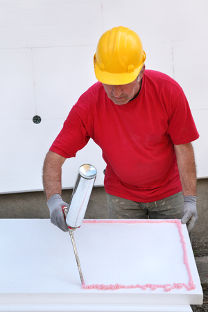Worker applying polyurethane expanding foam glue with gun applicator photo