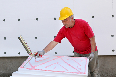 Worker applying polyurethane expanding foam glue with gun applicator