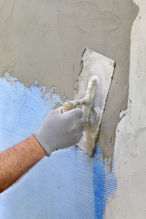 plasterboard: Worker spreading  mortar over plasterboard insulation and mesh  with trowel