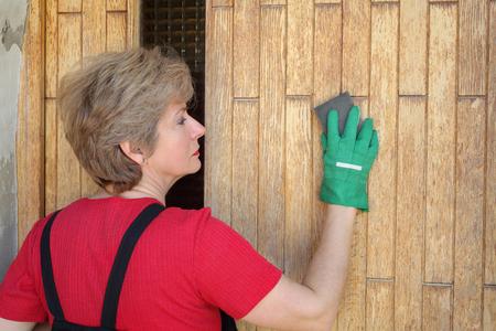 sanding block: Adult female worker  sanding wooden door with sanding block