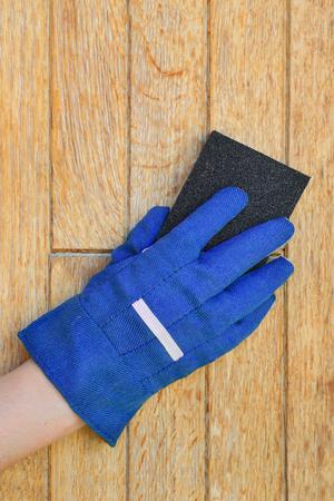 sanding block: Worker hand in glove sending wooden door with sanding block Stock Photo