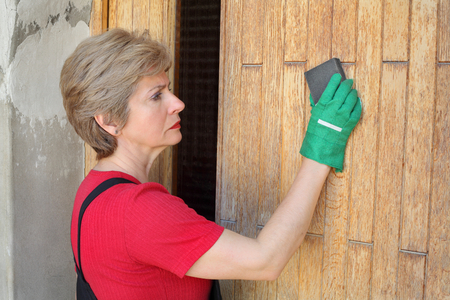 paintjob: Adult female worker  sanding wooden door with sanding block