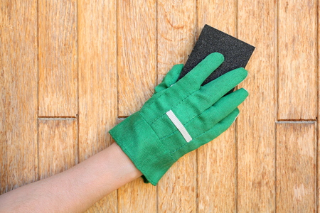 paintjob: Worker hand in glove sending wooden door with sanding block Stock Photo