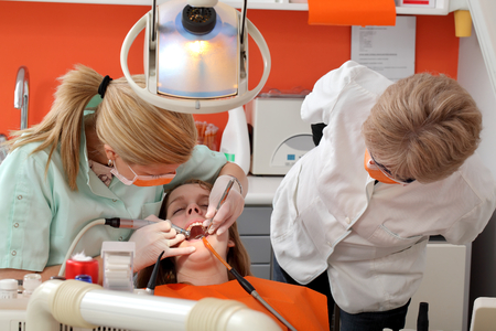 Dentist student drill  tooth of a young patient with professor looking Stockfoto