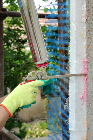 resistol: Trabajador de poliuretano aplicar la ampliación de la cola con aplicador de espuma de pistola Foto de archivo