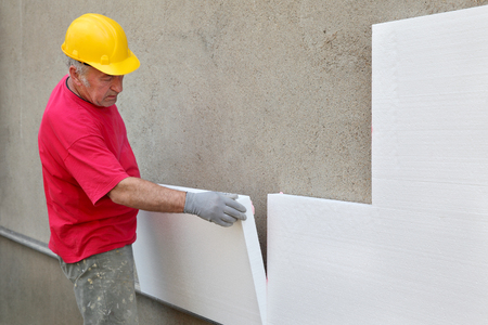 Worker placing styrofoam sheet insulation to wall at construction site Archivio Fotografico