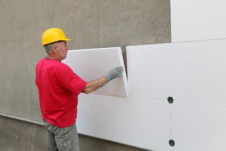 facade: Trabajador colocando la hoja de espuma de poliestireno aislante a la pared en el sitio de construcci�n