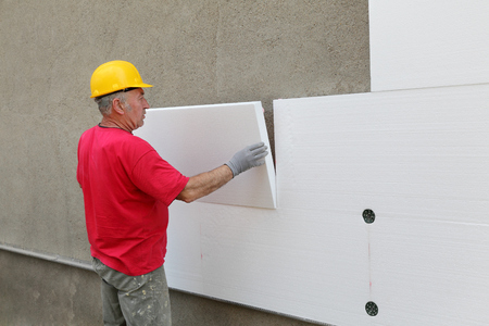 Worker placing styrofoam sheet insulation to wall at construction site Stockfoto