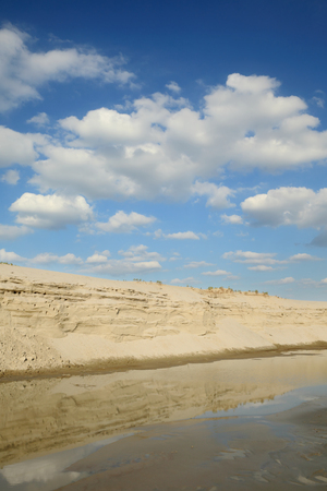 sand quarry: Sand quarry, heap of sand and puddle , landscape with beautiful sky
