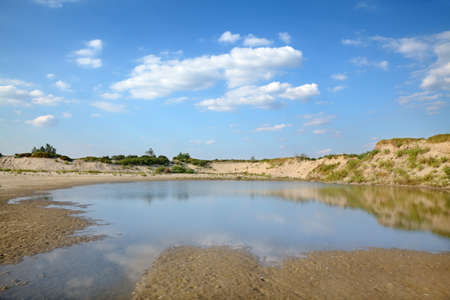 Marsh left after sand excavation, landscape with beautiful sky photo