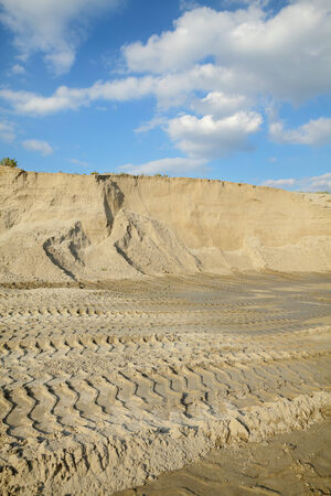sand quarry: Sand quarry, heap of sand with tire tracks, landscape with beautiful sky