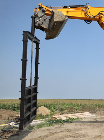 irrigated: Construction site of new irrigation channel in field, gate placing Stock Photo
