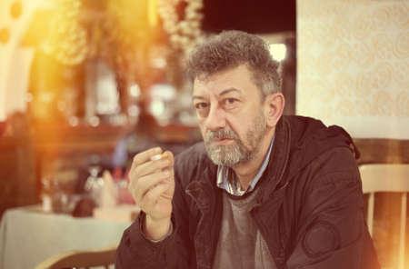 bad habit: Adult caucasian man with beard smoking cigarette vintage look of photo Stock Photo