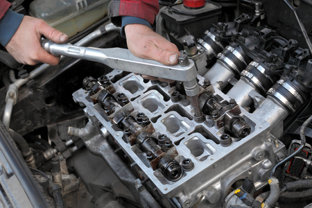 Mechanic fixing cylinder head with two camshaft of car engine with socket wrench