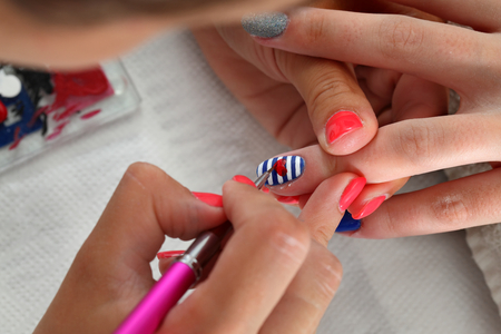 red nail colour: Finger nail treatment, painting heart with brush and lacquer Stock Photo