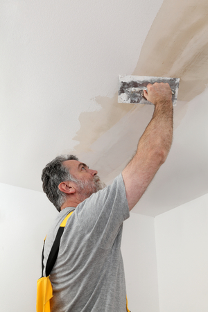 patching: Worker spreading  plaster to ceiling with trowel, repairing works