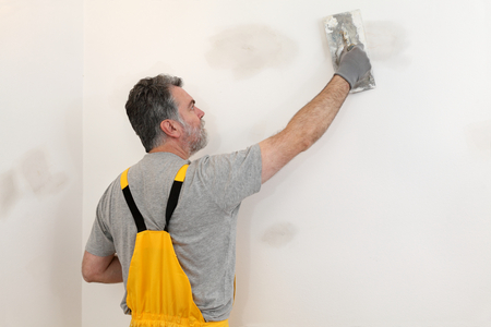 Worker spreading  plaster to wall with trowel, repairing works Stockfoto