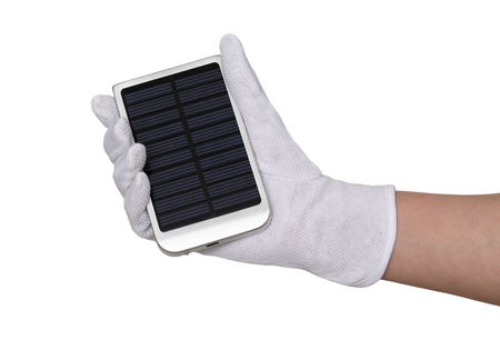Human hand in glove hold solar panel charger for cell phones photo