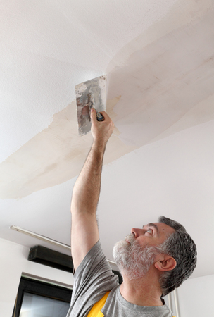 parget: Worker spreading  plaster to ceiling with trowel, repairing works