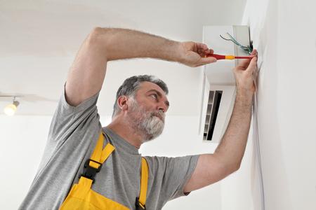 aire acondicionado: Electricista enchufe el�ctrico para la instalaci�n de aire acondicionado Foto de archivo