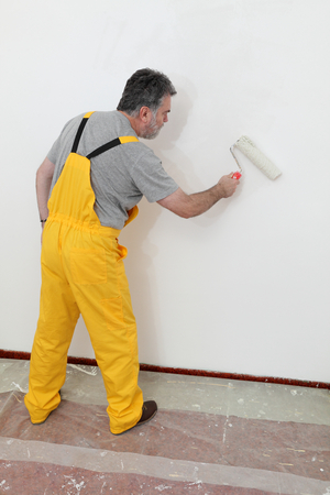 white color worker: Worker painting wall to white with paint roller