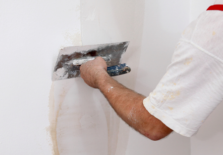 house painter: Worker spreading  plaster to wall with trowel, repairing works Stock Photo