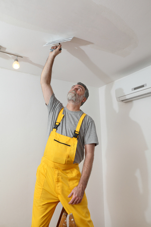 Worker spreading  plaster to ceiling with trowel, repairing works photo