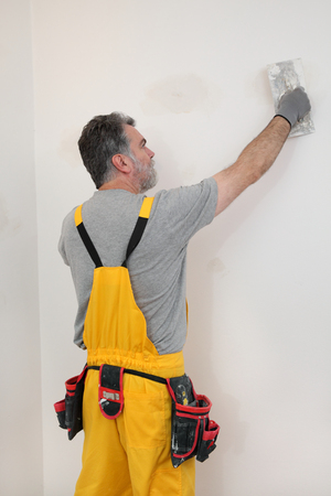 patching: Worker spreading  plaster to wall with trowel, repairing works Stock Photo