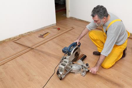 Worker cut wooden batten for laminate floor,  floating wood tile photo