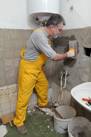 Worker spreading mortar with trowel to wall in a bathroom Imagens
