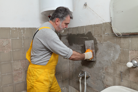 Worker spreading mortar with trowel to wall in a bathroom Standard-Bild