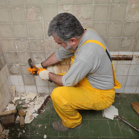 demolish: Adult worker remove, demolish old tiles in a bathroom with hammer and chisel Stock Photo