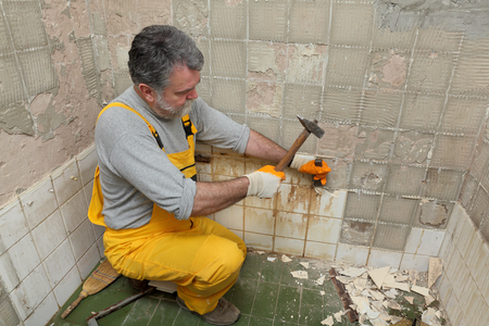 Adult worker remove, demolish old tiles in a bathroom with hammer and chisel Stockfoto