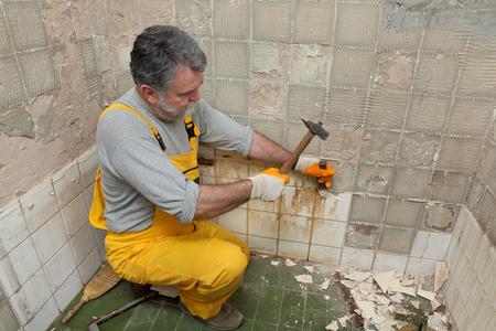 Volwassen werknemer verwijderen, slopen oude tegels in een badkamer met hamer en beitel