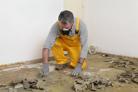 clean carpet: Adult worker with protective mask remove glue and rubber with putty knife from floor