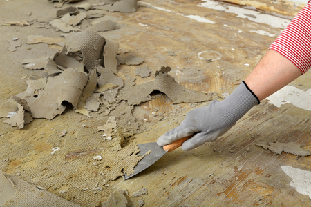 putty: Worker removes glue and rubber with putty knife from floor Stock Photo