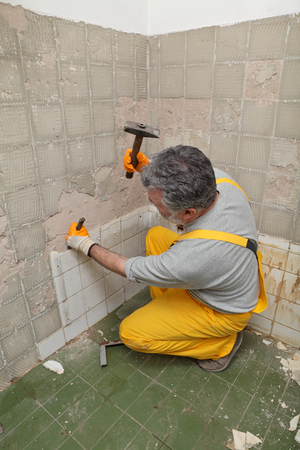 Adult worker remove, demolish old tiles in a bathroom with hammer and chisel photo