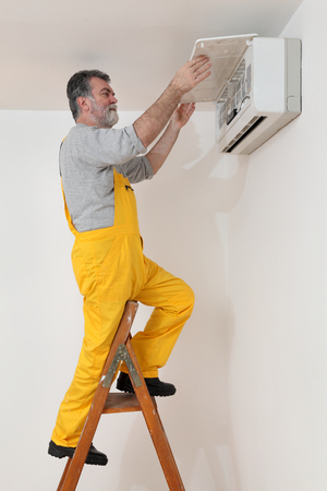 setup man: Electrician examine or install air condition device in a room