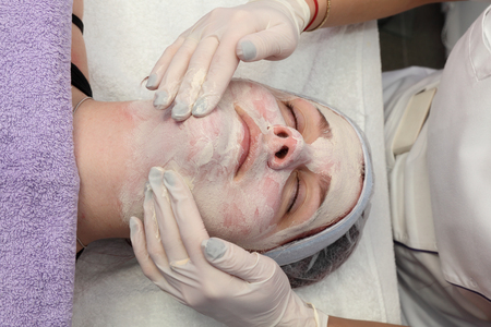 cosmetician: Skin treatment, beautician applying cream to face of young female, real people